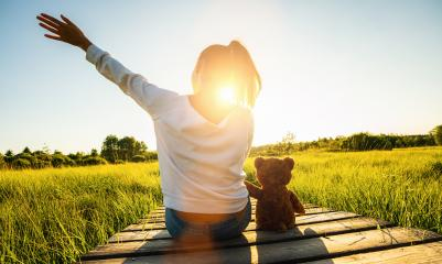Woman sit on a boardwalk and holding a teddy bear toy at sunset, copyspace for your individual text.- Stock Photo or Stock Video of rcfotostock | RC-Photo-Stock