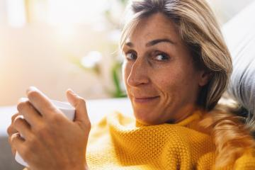Woman sitting on the couch with a cup in her hands and smiling as she looks in front of her, relaxation concept image- Stock Photo or Stock Video of rcfotostock   RC-Photo-Stock