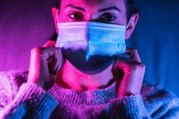 woman wearing anti virus face mask protection in colourful bright neon uv lights posing at home  : Stock Photo or Stock Video Download rcfotostock photos, images and assets rcfotostock | RC-Photo-Stock.: