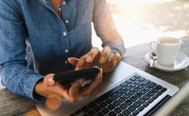 Young business woman in jeans dress sitting at table in cafe and writing at smartphone. On table is laptop and cup of coffee. Freelancer working in coffee shop. Student learning online.- Stock Photo or Stock Video of rcfotostock | RC-Photo-Stock