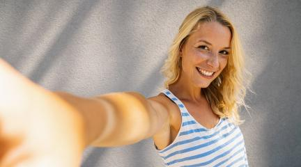 Young cheerful girl smiling and taking selfie with smartphone, on summer in city street. Urban life concept image- Stock Photo or Stock Video of rcfotostock | RC-Photo-Stock