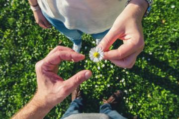 young couple in sneakers stands opposite on daisy Meadow and enjoying the love of nature, high angle footsie or flortrait, personal pespective from above.- Stock Photo or Stock Video of rcfotostock | RC-Photo-Stock