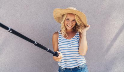 Young girl smiling and use selfie stick to take a selfie, on summer in city street. Urban life concept.- Stock Photo or Stock Video of rcfotostock | RC-Photo-Stock