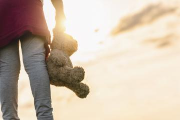 Young Girl standin through a sunset and Carrying a Teddy Bear- Stock Photo or Stock Video of rcfotostock | RC-Photo-Stock