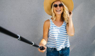 Young girl with straw hat smiling and use selfie stick to take a selfie, on summer in city street. Urban life concept image : Stock Photo or Stock Video Download rcfotostock photos, images and assets rcfotostock | RC-Photo-Stock.: