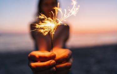 Young happy woman stands on beach with sparkler in sunset light- Stock Photo or Stock Video of rcfotostock | RC-Photo-Stock