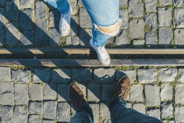 young man and a girl in sneakers stands opposite on cobblestones on a train track, high angle footsie or flortrait, personal pespective from above.- Stock Photo or Stock Video of rcfotostock | RC-Photo-Stock