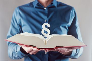 young man holding book with paragraph sign - law concept image- Stock Photo or Stock Video of rcfotostock | RC-Photo-Stock
