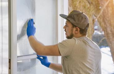 young man is using a rag and squeegee while cleaning windows.- Stock Photo or Stock Video of rcfotostock | RC-Photo-Stock