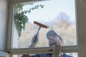 young man is using a rag and squeegee while cleaning windows. professional window cleaner : Stock Photo or Stock Video Download rcfotostock photos, images and assets rcfotostock | RC-Photo-Stock.:
