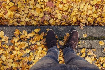 Young man stands in at a curbstone with foliage leafs at autumn on the streets, personal pespective from above.- Stock Photo or Stock Video of rcfotostock | RC-Photo-Stock