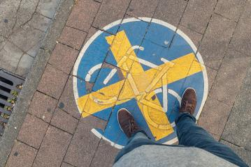young man stands on a Bicycle path with cross sign at a sidewalk, high angle footsie or flortrait, personal pespective from above.- Stock Photo or Stock Video of rcfotostock | RC-Photo-Stock
