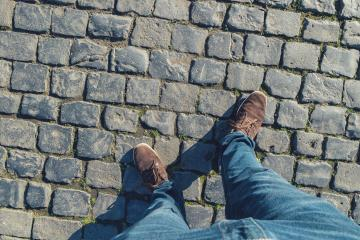 young man stands on cobblestones, high angle footsie or flortrait, personal pespective from above.- Stock Photo or Stock Video of rcfotostock   RC-Photo-Stock