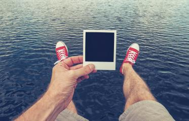 Young man with Picture Frame in his hand sitting above the ocean, Point Of View Shot.- Stock Photo or Stock Video of rcfotostock | RC-Photo-Stock