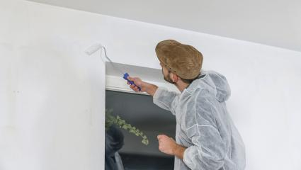 young painter working with paint roller to paint the corner of a room window with white color- Stock Photo or Stock Video of rcfotostock | RC-Photo-Stock