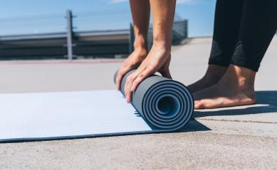 young woman folding blue yoga or fitness mat after working out. keep fit concepts image. copyspace for your text.- Stock Photo or Stock Video of rcfotostock | RC-Photo-Stock