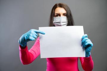 Young woman in medical mask and gloves showing empty blank paper in her hands. Focus on a piece of paper. prevent others from corona COVID-19 and SARS cov 2 infection, copy space for individual text- Stock Photo or Stock Video of rcfotostock | RC-Photo-Stock