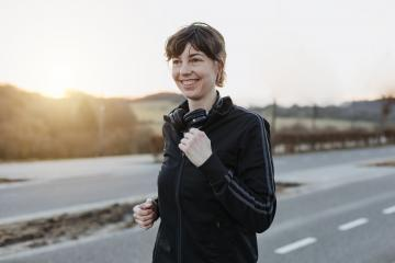Young woman is jogging outside on the street. The athletic person is full of motivation and happy. : Stock Photo or Stock Video Download rcfotostock photos, images and assets rcfotostock | RC-Photo-Stock.: