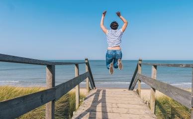 Young Woman Jumps on Beach over a wooden path to the Baltic sea on a summer day- Stock Photo or Stock Video of rcfotostock | RC-Photo-Stock