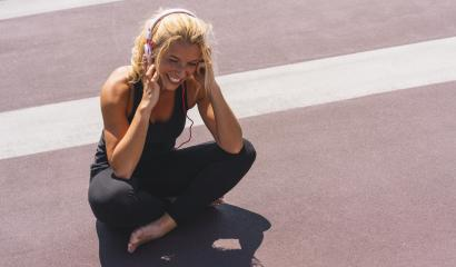 Young woman listening to music with earphones for fitness motivation. Portrait of a smiling young woman in sportswear relaxing sitting getting inspired. copyspace for your individual text.- Stock Photo or Stock Video of rcfotostock | RC-Photo-Stock