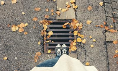 Young woman standing at autumn on a manhole cover at the streets, personal pespective from above.- Stock Photo or Stock Video of rcfotostock | RC-Photo-Stock