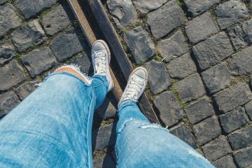 Young woman stands cobblestones on a train track, personal pespective from above.- Stock Photo or Stock Video of rcfotostock | RC-Photo-Stock