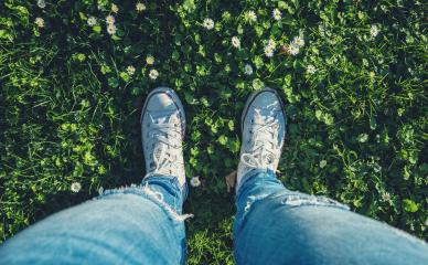 young woman stands in sneakers in a Daisy meadow at spring, high angle footsie or flortrait, personal pespective from above.- Stock Photo or Stock Video of rcfotostock | RC-Photo-Stock