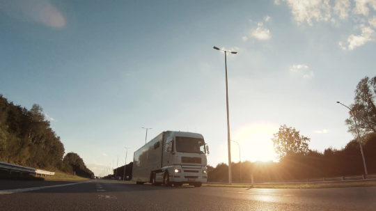 Cargo truck with cargo trailer driving on a highway. White Truck delivers goods in early hours of the Morning - very low angle drive thru close up shot.- Stock Photo or Stock Video of rcfotostock | RC-Photo-Stock