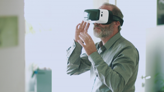 Mature business man wearing virtual reality googles / VR Glasses to work with in modern bright office- Stock Photo or Stock Video of rcfotostock | RC-Photo-Stock