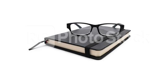closed black cover notebook with glasses on white  background  : Stock Photo or Stock Video Download rcfotostock photos, images and assets rcfotostock | RC-Photo-Stock.: