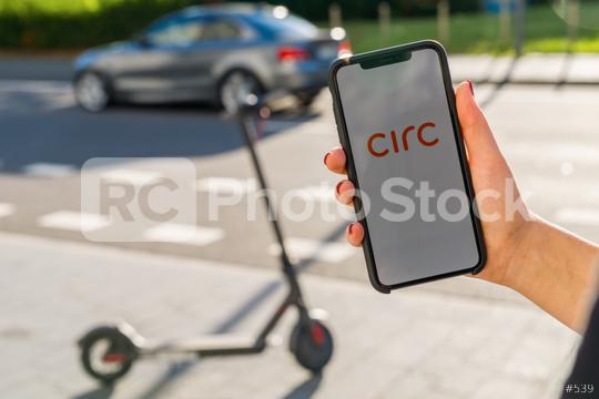 BERLIN, GERMANY AUGUST 2019: Woman hand holding iphone Xs with logo of CIRC app displayed on a smartphone to rent a e-Scooter. Circ is a rental electric scooter company. Quick and easy way to travel  : Stock Photo or Stock Video Download rcfotostock photos, images and assets rcfotostock | RC-Photo-Stock.: