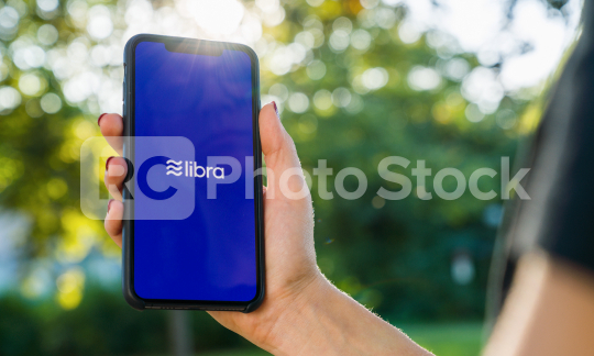 BERLIN, GERMANY AUGUST 2019: Woman hand holding iphone Xs with logo of Libra in the park. Libra Facebook cryptocurrency and bitcoin cryptocurrency smartphone share, Libra coins concept.  : Stock Photo or Stock Video Download rcfotostock photos, images and assets rcfotostock | RC-Photo-Stock.: