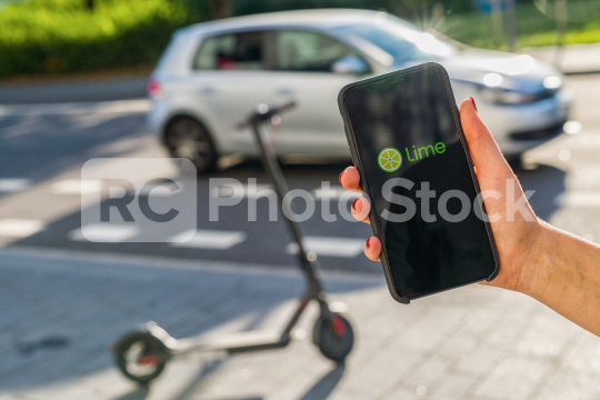BERLIN, GERMANY AUGUST 2019: Woman hand holding iphone Xs with logo of LIME app displayed on a smartphone to rent a e-Scooter. Lime is a rental electric scooter company. Quick and easy way to travel  : Stock Photo or Stock Video Download rcfotostock photos, images and assets rcfotostock   RC-Photo-Stock.: