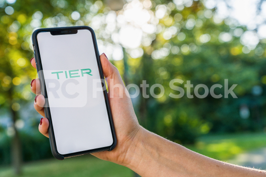 BERLIN, GERMANY AUGUST 2019: Woman hand holding iphone Xs with logo of TIER app displayed on a smartphone to rent a e-Scooter. Tier is a rental electric scooter company. Quick and easy way to travel  : Stock Photo or Stock Video Download rcfotostock photos, images and assets rcfotostock   RC-Photo-Stock.: