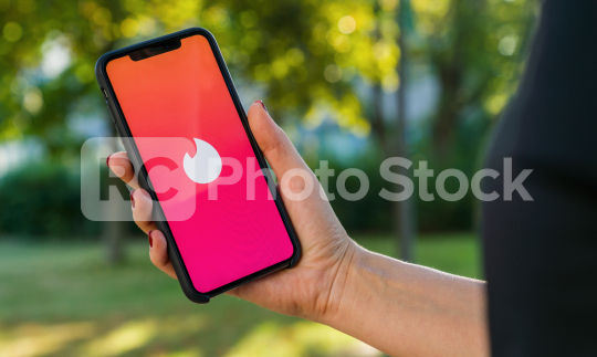 BERLIN, GERMANY AUGUST 2019: Woman hand holding iphone Xs with logo of Tinder app to log in. Tinder is a multiplatform people localization application for online romantic dating. It is very famous.  : Stock Photo or Stock Video Download rcfotostock photos, images and assets rcfotostock   RC-Photo-Stock.: