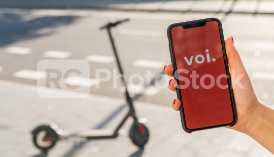 BERLIN, GERMANY AUGUST 2019: Woman hand holding iphone Xs with logo of VOI app displayed on a smartphone to rent a e-Scooter. Voi is a rental electric scooter company. Quick and easy way to travel.   : Stock Photo or Stock Video Download rcfotostock photos, images and assets rcfotostock | RC-Photo-Stock.: