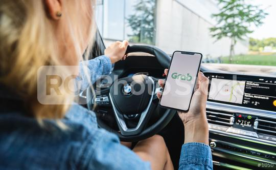 BERLIN, GERMANY JULY 2019: Woman hand holding iphone Xs with logo of Grab application in a car. Grab is smartphone app all-in-one transport booking in South-East Asia.  : Stock Photo or Stock Video Download rcfotostock photos, images and assets rcfotostock | RC-Photo-Stock.: