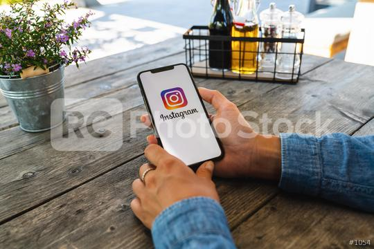 BERLIN, GERMANY JULY 2019: Woman hand holding iphone Xs with logo of instagram application in a restaurant. Instagram is largest and most popular photograph social networking.  : Stock Photo or Stock Video Download rcfotostock photos, images and assets rcfotostock | RC-Photo-Stock.: