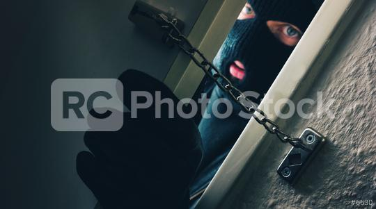 Burglar in a Mask Breaking Into the House door with door chain  : Stock Photo or Stock Video Download rcfotostock photos, images and assets rcfotostock | RC-Photo-Stock.: