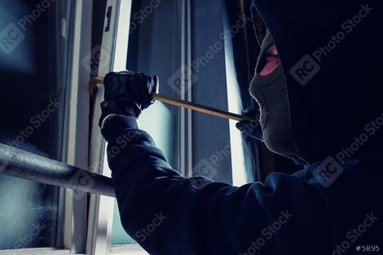 burglar using crowbar to break into a victim