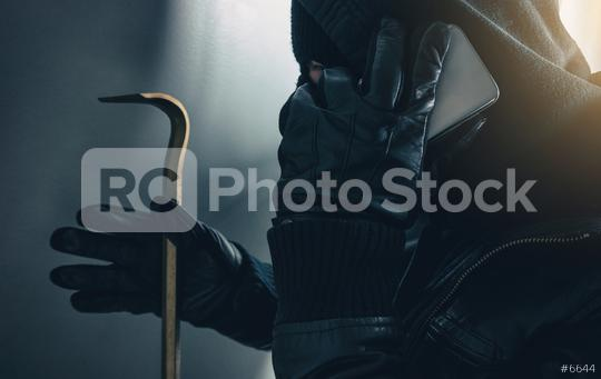 burglar with crowbar use a smartphone to communicate a burglary   : Stock Photo or Stock Video Download rcfotostock photos, images and assets rcfotostock | RC-Photo-Stock.: