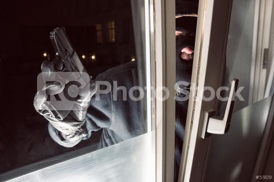 Burglar with gun looking at a window to breaking and entering a victim