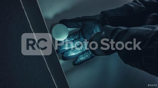 burglar with leather gloves and torch opens a victim
