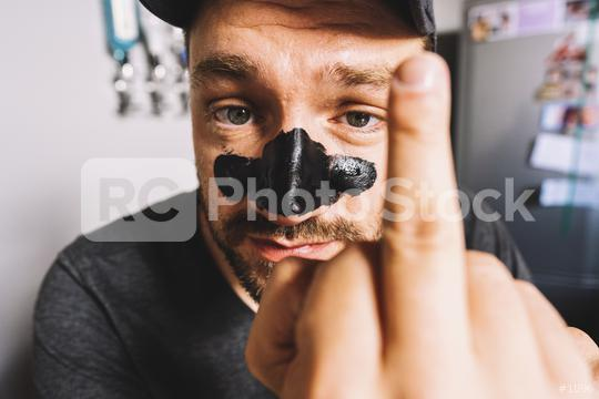 close up of man showing middle finger hand sign and black Mask Peeling cosmetic - gesture, morals and people concept  : Stock Photo or Stock Video Download rcfotostock photos, images and assets rcfotostock | RC-Photo-Stock.: