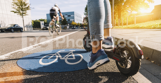 Close up of woman start to riding a electric scooter or kick scooter at cityscape on a Bicycle road sign way  : Stock Photo or Stock Video Download rcfotostock photos, images and assets rcfotostock | RC-Photo-Stock.:
