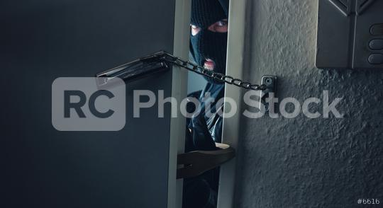 dangerous masked burglar with crowbar breaking into a victim