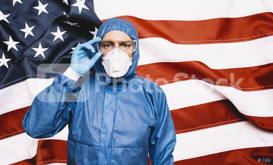 Doctor wearing protection Suit for Fighting Covid-19 (Corona virus) SARS infection Protective Equipment (PPE), Against The American Flag Banner.   : Stock Photo or Stock Video Download rcfotostock photos, images and assets rcfotostock   RC-Photo-Stock.:
