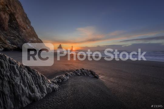 Fels am Strand Reynisfjara mit Blick auf Reynisdrangar zum Sonnenaufgang im Winter  : Stock Photo or Stock Video Download rcfotostock photos, images and assets rcfotostock | RC-Photo-Stock.: