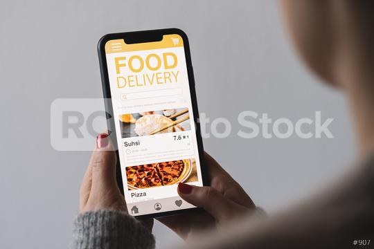Food delivery app on a mobile phone. Restaurant order online. Woman using smartphone to get take away lunch home delivered. Fast courier service. Suhsi and Pizza menu mock up in cellphone screen.  : Stock Photo or Stock Video Download rcfotostock photos, images and assets rcfotostock   RC-Photo-Stock.: