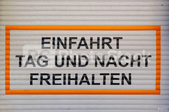 German text Einfahrt Tag und Nacht freihalten, translate  keep the drive free day and night, parking forbidden sign on a garage door.   : Stock Photo or Stock Video Download rcfotostock photos, images and assets rcfotostock | RC-Photo-Stock.: